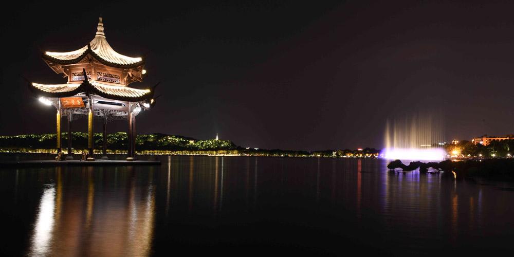 Turistas apreciam a vista noturna do Lago do Oeste em Hangzhou