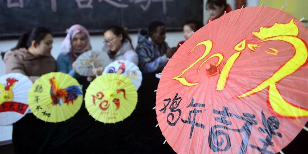 Estudantes internacionais pintam temas de galo em sombrinhas de papel chinesas