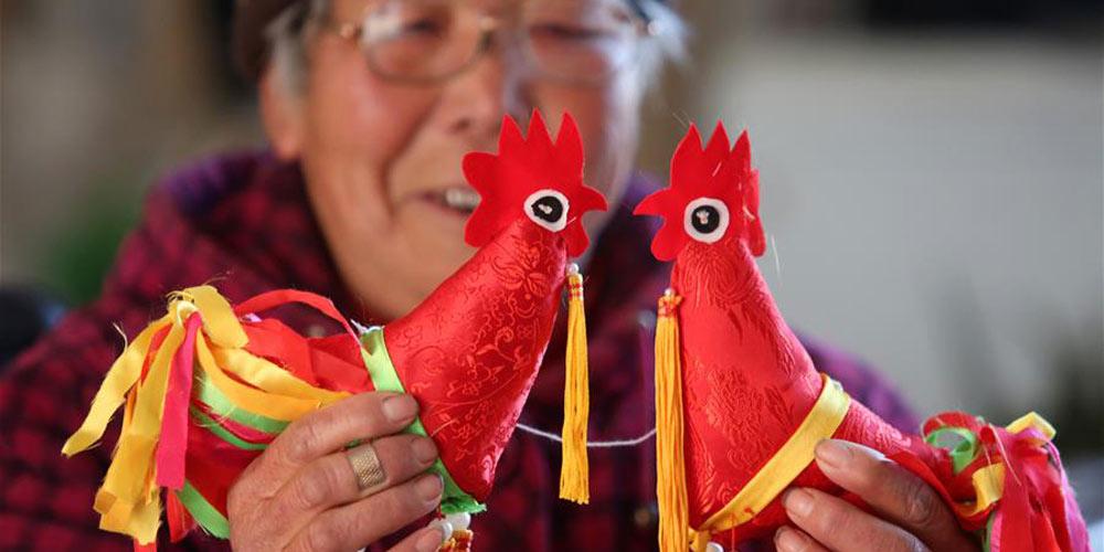 Artista popular Du Yifang faz bonecos de galo para trazer boa sorte no ano novo