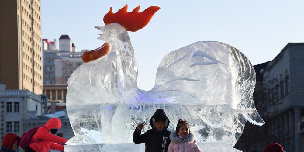Turistas posam para fotos em frente à escultura de gelo, no nordeste da China