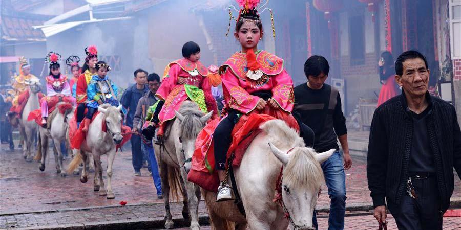 Crianças se vestem de figuras lendárias em desfile a cavalos no sudeste da China