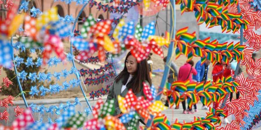 Pessoas visitam decorações de cata-ventos em Dalian