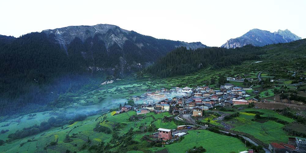 Paisagem das montanhas Zhagana caracterizada por aldeias de estilo tibetano
