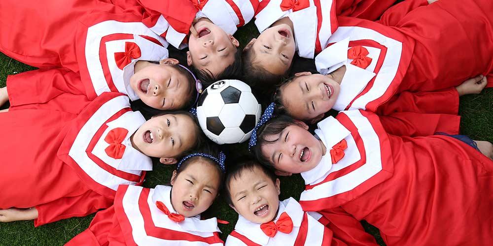 Crianças chinesas tiram fotos para formatura do jardim de infância