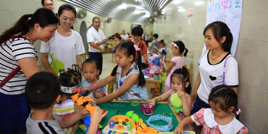 Crianças vendem brinquedos usados em mercado de pulgas em Chongqing