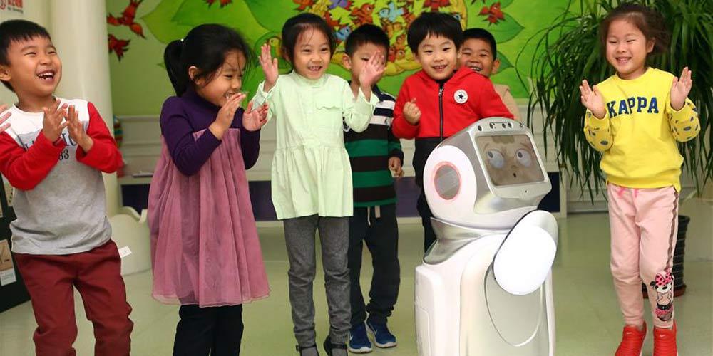 Crianças brincam com robô educacional interativo em jardim de infância em Tianjin