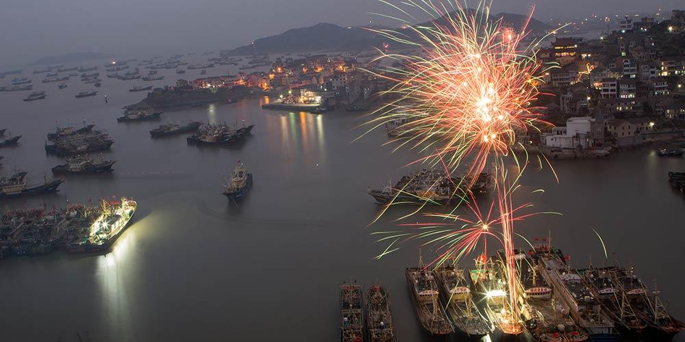 Fogos de artifício iluminam céu em porto pesqueiro em celebração ao Ano Novo Lunar chinês