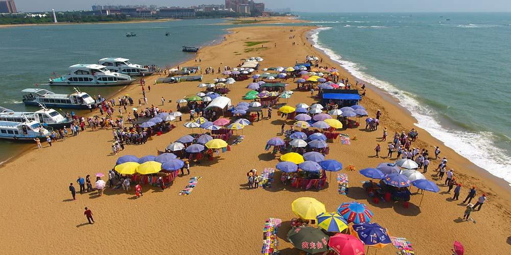 Turistas se divertem na praia Yudai em Boao, sul da China