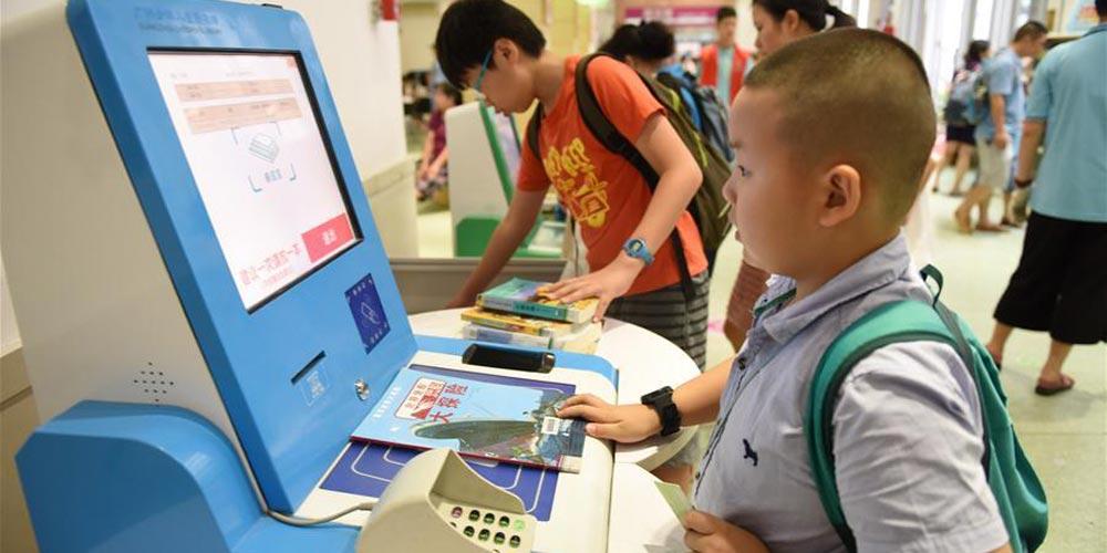 Crianças leem livros na biblioteca para enriquecer as férias de verão na China