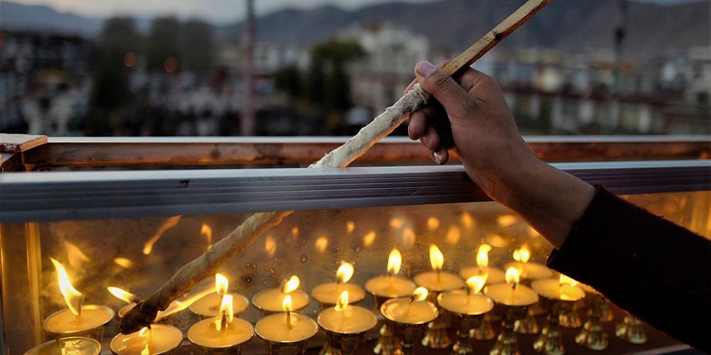 Pessoas acendem lâmpadas de manteiga de iaque em comemoração a mestre do budismo tibetano
