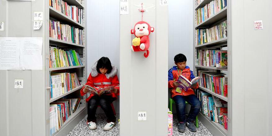 Crianças migrantes se divertem em biblioteca na aldeia Changli em Shaanxi, noroeste da China