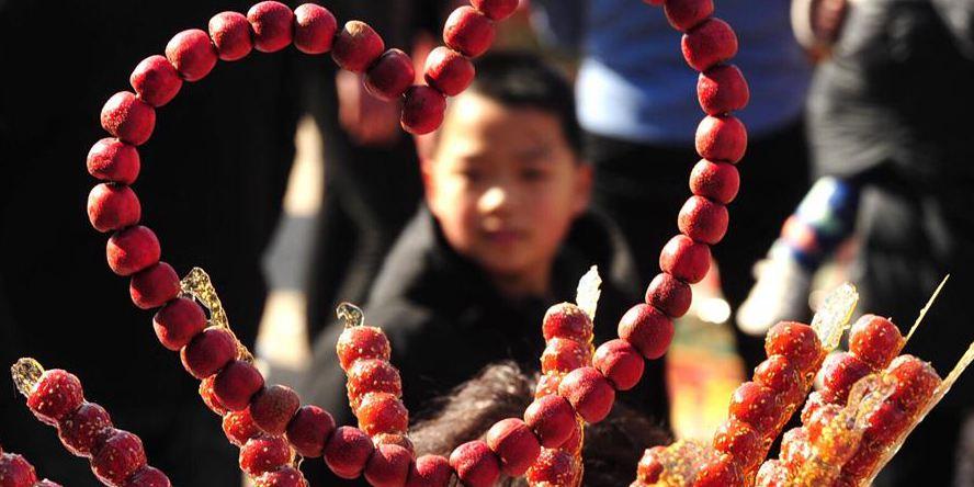 Pessoas compram tanghulu durante atividade para comemorar Festival das Lanternas em Hebei