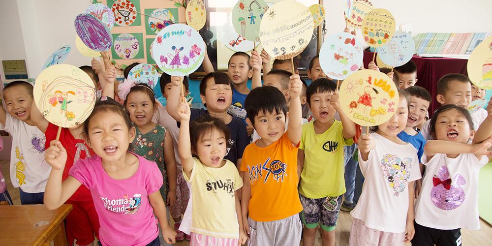 Crianças fazem leques tradicionais chineses para celebrar o solstício de verão em Beijing