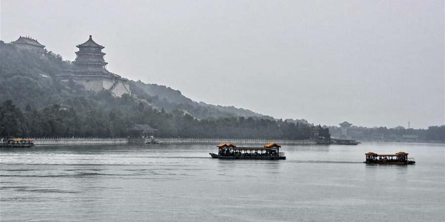Fotos: visitantes andam de barcos durante chuva no Palácio de Verão em Beijing