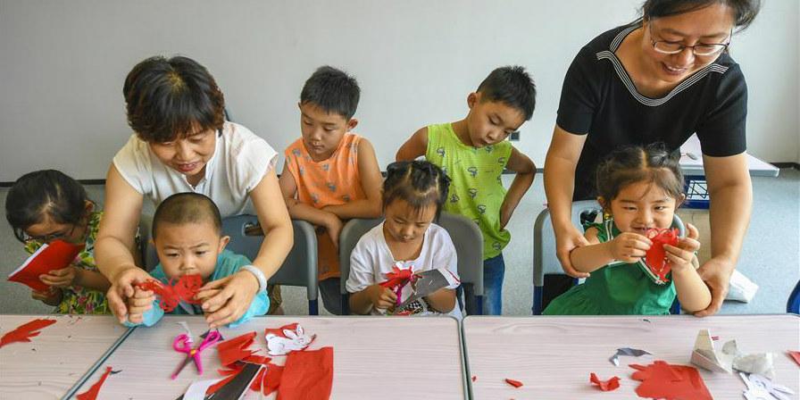 Artista folclórica ensina crianças a fazer corte de papel em Hebei