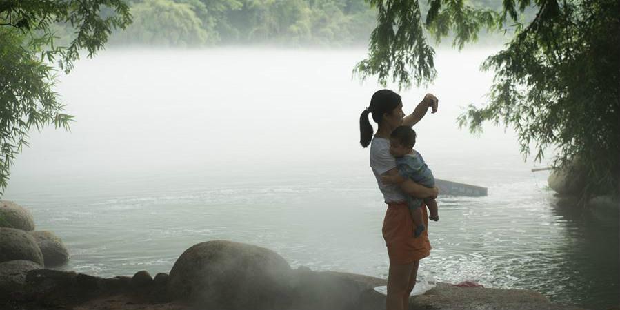 Pessoas aproveitam frescura na beira do rio Xin'an em Jiande, leste da China