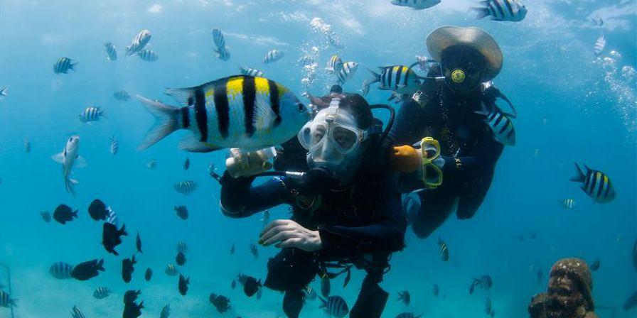 Turistas desfrutam do mergulho no ponto turístico Ilha de Boundary em Hainan