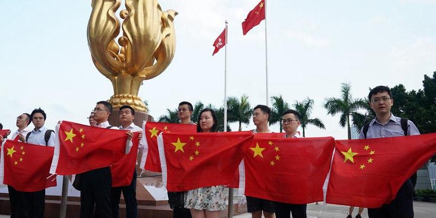Jovens seguram bandeira nacional da China durante mobilização relâmpago em Hong Kong