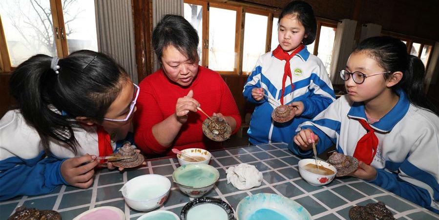 Alunos aprendem técnicas do cloisonné no distrito de Xianghe