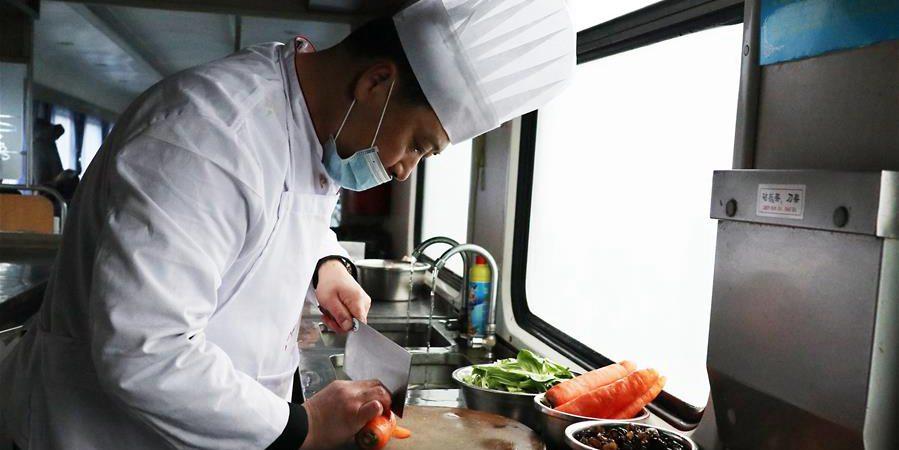 Alta temporada de viagens da Festa da Primaver: chef prepara comida para passageiros ferroviários
