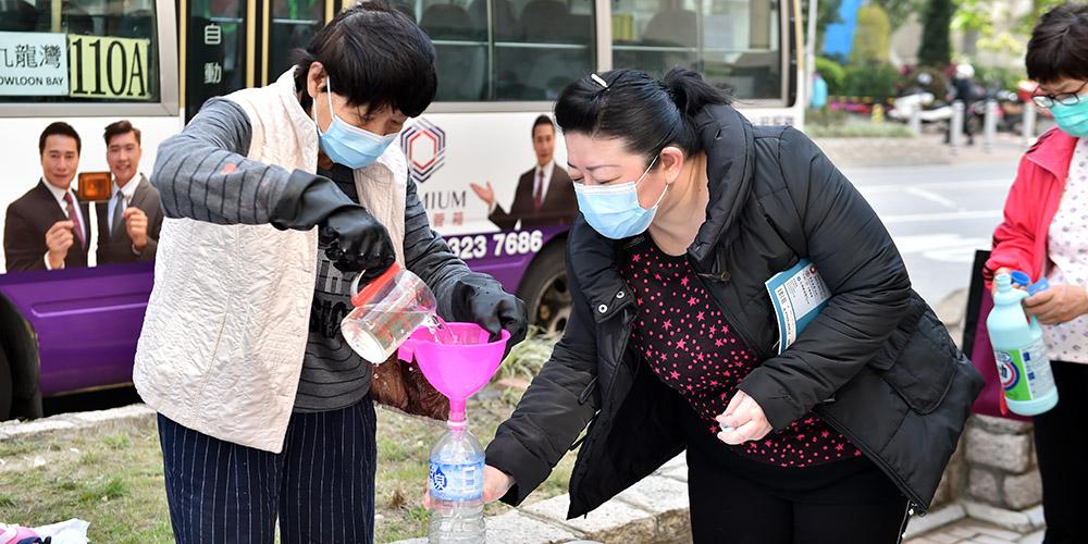 Moradores locais recebem desinfetante distribuído gratuitamente pela Federação dos Sindicatos de Hong Kong