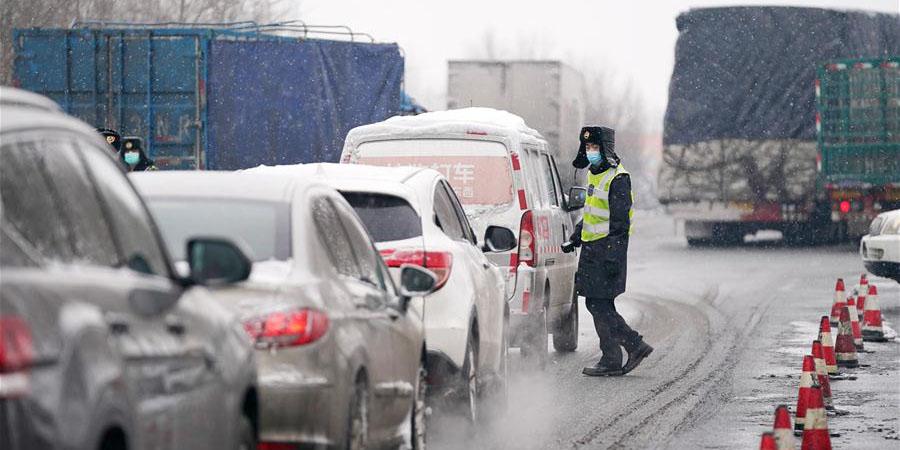 Funcionários e voluntários trabalham na neve em pontos de controle para prevenção do novo coronavírus em Harbin