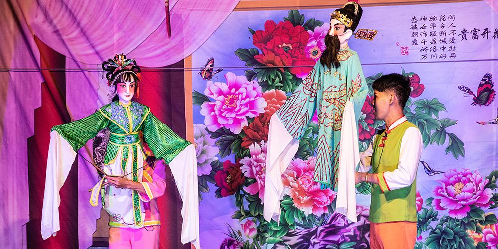 Artistas folclóricos realizam show de fantoches no distrito de Lingao, província de Hainan