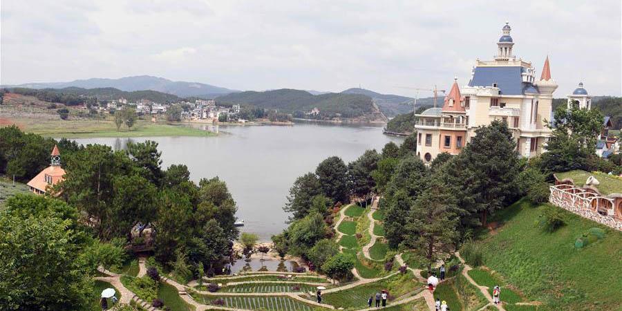 Turistas aproveitam tempo de lazer em Fenglongwan, província de Yunnan