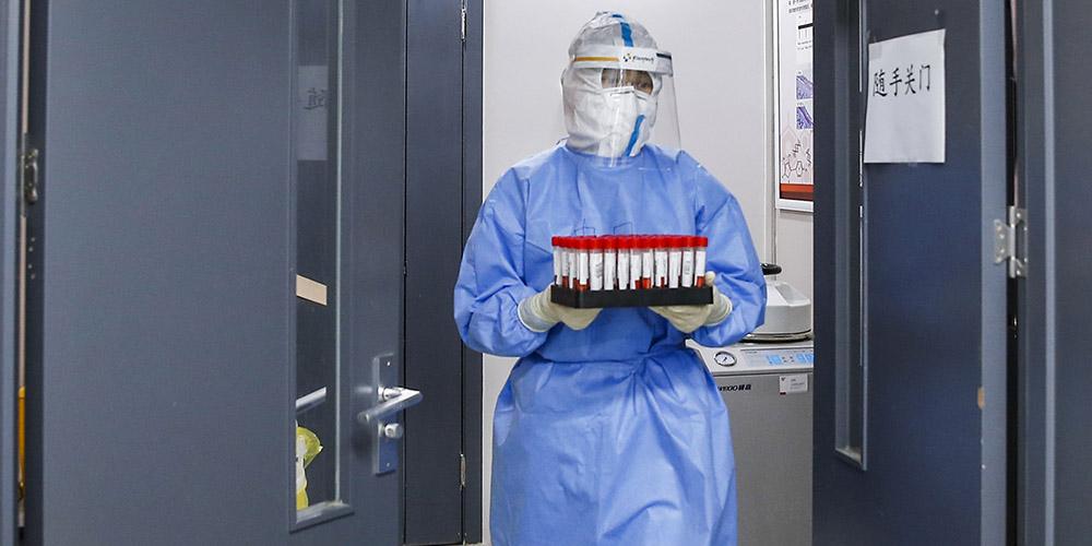 Funcionários de saúde conduzem teste de ácido nucleico para COVID-19 em Beijing