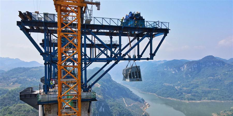 Selas de apoio são instaladas no topo da torre principal da Grande Ponte do Lago Kaizhou da via expressa Weng'an-Kaiyang
