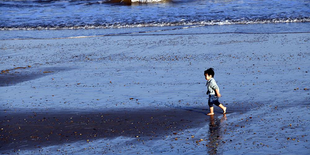 Pessoas se divertem em praia de Rizhao