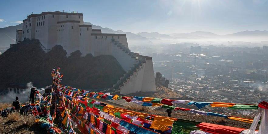 Pessoas penduram novas bandeiras de oração para rezar pela paz e prosperidade no Tibet