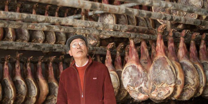 Pessoas trabalham em fábrica de presunto em Jinhua, província de Zhejiang